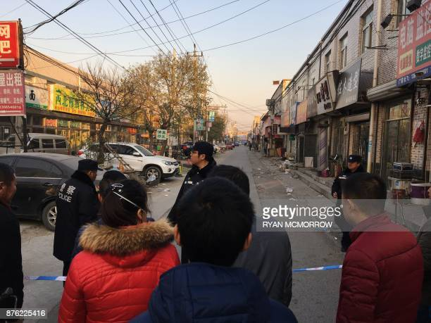 Residents look on as police stand guard near the site of a fatal housing block fire in Beijing on November 19 2017 Chinese authorities on November 19...