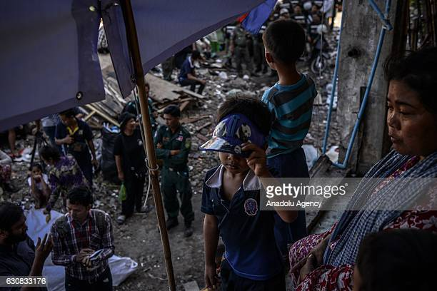 Residents look on as polices gather outside one of the squatted apartments during a protest at the Borei Keila site in Phnom Penh Cambodia on January...