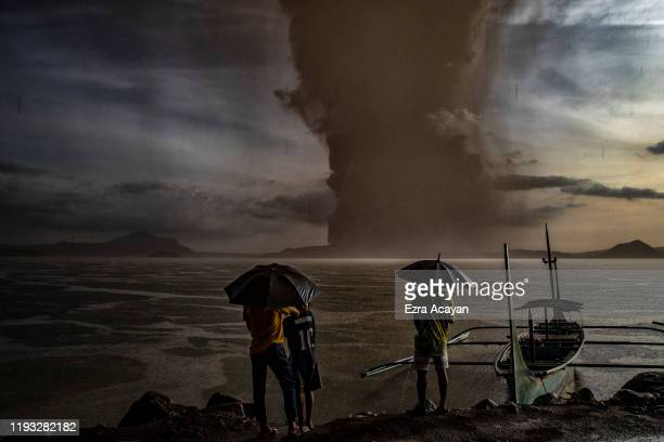 Residents look on as Taal Volcano erupts on January 12, 2020 in Talisay, Batangas province, Philippines. Local authorities have begun evacuating...
