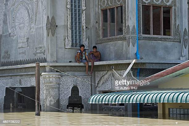 Residents look on from a floodinundated building in Kalay upper Myanmar's Sagaing region on August 2 2015 The toll from flash floods and landslides...