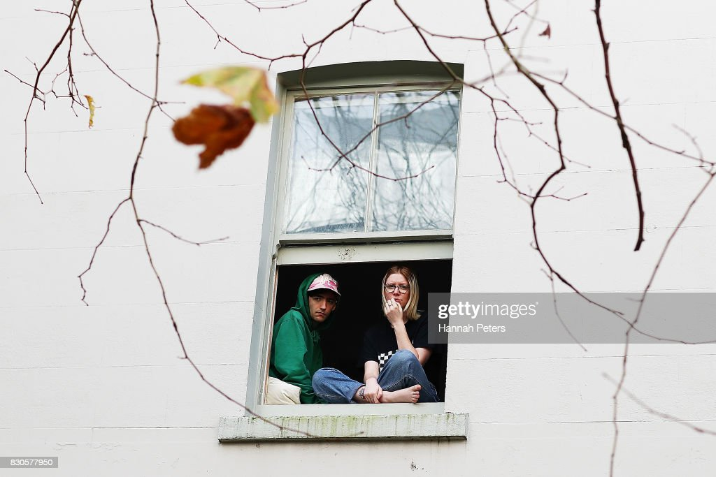 Residents look on from their window during a rally for pay equity in New Zealand on August 12, 2017 in Auckland, New Zealand. Opposition MPs and members of the public are protesting against the government's Pay Equity Bill ahead of its anticipated first reading in parliament on Tuesday.