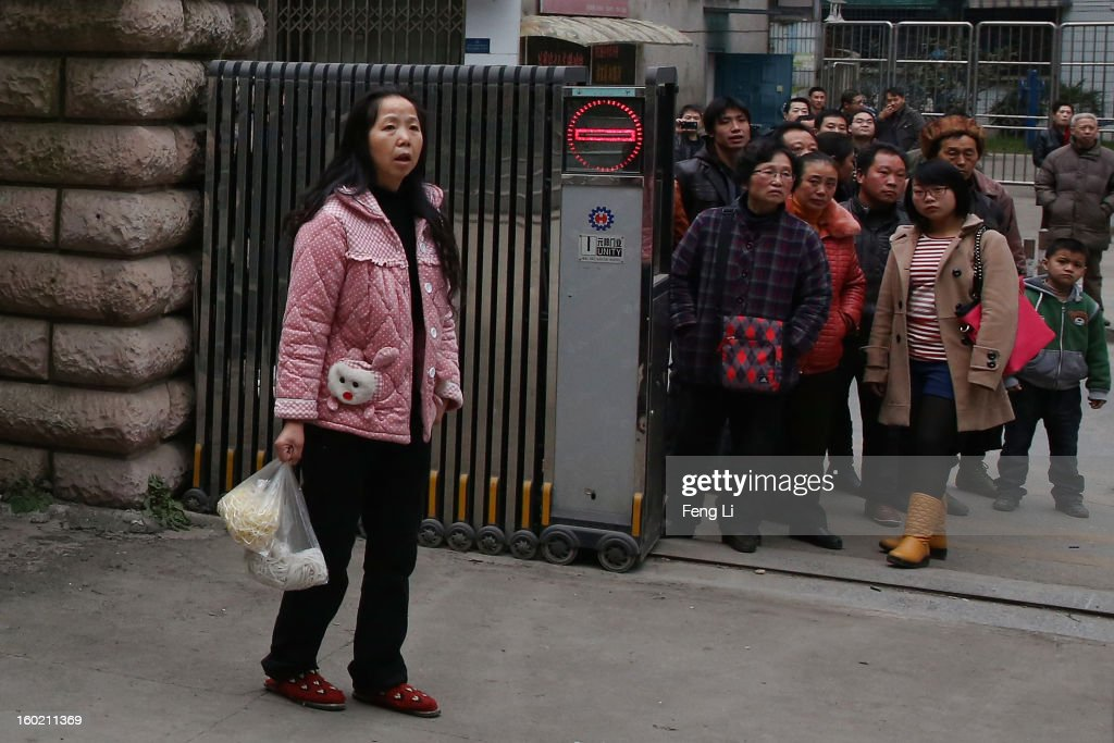 Residents look on outside Guiyang Intermediate People's Court as media rushing into the court yard before a press conference on former Chinese leader Bo Xilai's case on January 28, 2013 in Guiyang, China. 'It is fake information. The trial of Bo Xilai will not open in Guiyang today', Vice-president of Guiyang Intermediate People's Court Jiang Hao said. The trial of Bo Xilai is expected to open after the 'two sessions' in March, China's official newspaper Global Times reports on Monday.