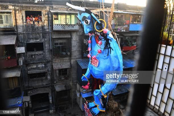 Residents look out from a window to a Holika Dahan effigy of the Coronavirus demon Coronasur ahead of the Hindu festival of Holi in Mumbai on March 9...