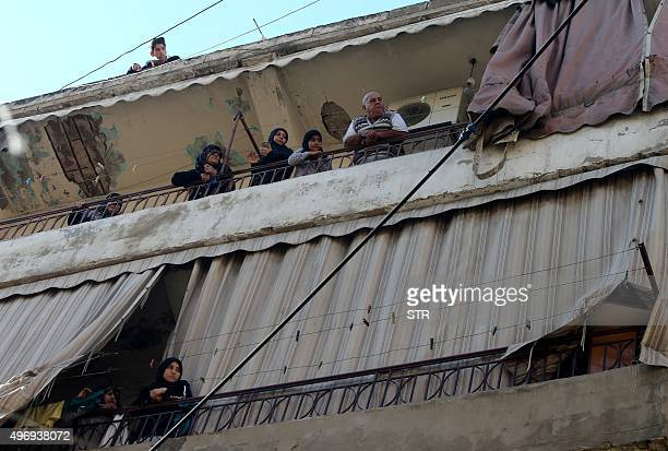 Residents look out from their balcony at Lebanese forensic police and security forces investigating the site of a twin bombing attack that rocked a...