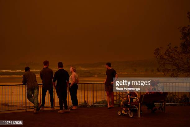 Residents look out over the beach as thick smoke covers the skyline on January 04, 2020 in Tuross Head, Australia. A state of emergency has been...
