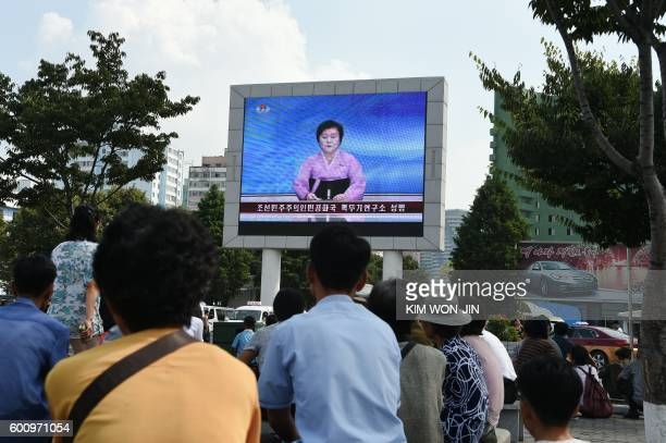 TOPSHOT Residents look up at a big screen TV in front of Pyongyang railway station showing television presenter Ri ChunHee officially announcing that...