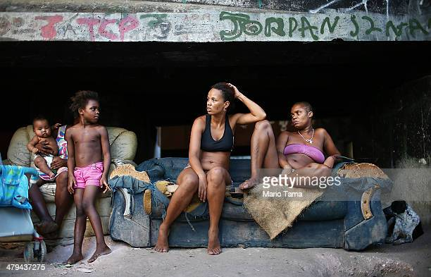 Residents Luiza Janubie Leiticia and Lucas sit beneath an overpass near their houses in an impoverished area in the unpacified Complexo da Mare slum...