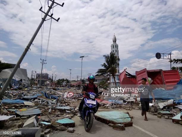 TOPSHOT Residents make their way along a street full of debris after an earthquake and tsunami hit Palu on Sulawesi island on September 29 2018...