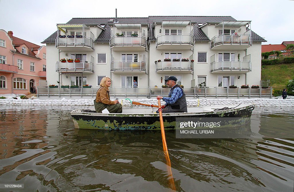 Residents make their way in a boat through the flood water in the eastern German city of Eisenhuettestadt as the river Oder floods the aera near the Polish border on May 28, 2010. Torrential rain in Poland's mountainous south have caused rivers swell and the flood warning level has risen in Germany.