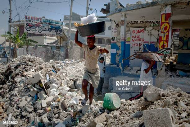 Residents make their way through debris March 30 2010 in the Bel Air section of PortauPrince Haiti Haitian President Rene Preval will unveil $39...