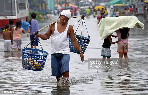 Residents make their way through flood water that partially submerged shanty houses in Malabon 25 July 2006 following continious rain brought by...