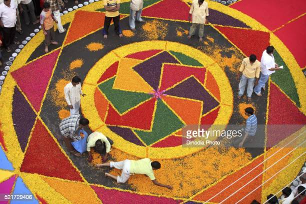 Residents making colourful flower Rangoli on road for immersion celebration of Lord Ganesh, Sangli, Maharashtra, India