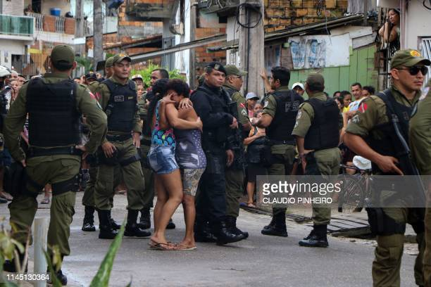 TOPSHOT Residents mourn surrounded by police officers outside a bar as corpses are removed after a shooting in Belem Para state Brazil on May 19 2019...