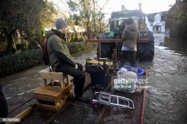 Residents near the village of Muchelney Somerset hitch a ride on a tractor trailer through flooded roads to reach unblocked roads after homes were...