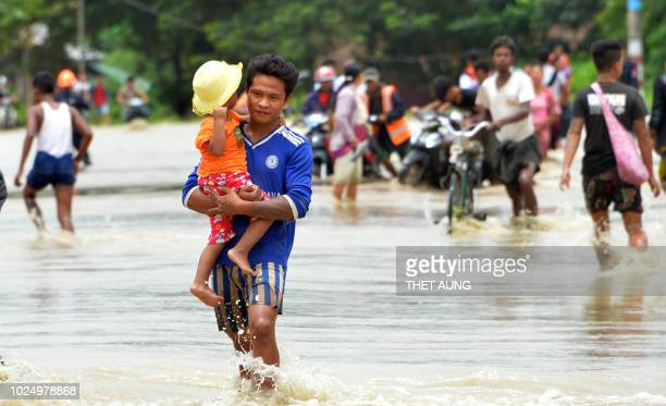 Residents negotiate a flooded road after rampaging waters from Swar Chaung dam submerged villages in Bago region central Myanmar on August 29 2018