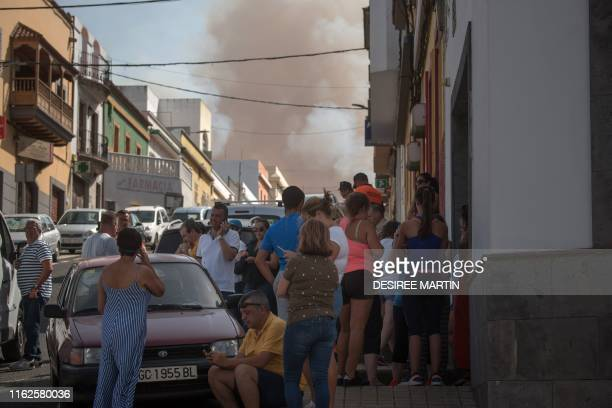Residents observe smoke billowing from a forest fire raging near Montana Alta on the island of Gran Canaria on August 18 2019 Authorities on the...