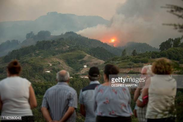 Residents observe smoke billowing from a forest fire raging near Montana Alta on the island of Gran Canaria on August 18, 2019. - Authorities on the...