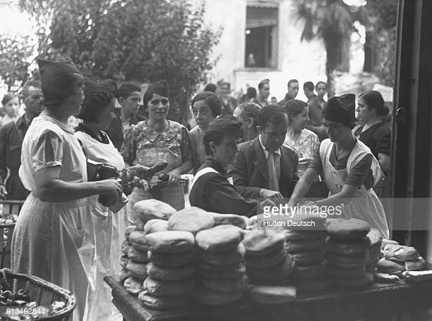 Residents obtain their rations at a food distribution centre in Madrid during the Spanish Civil War | Location Madrid Spain