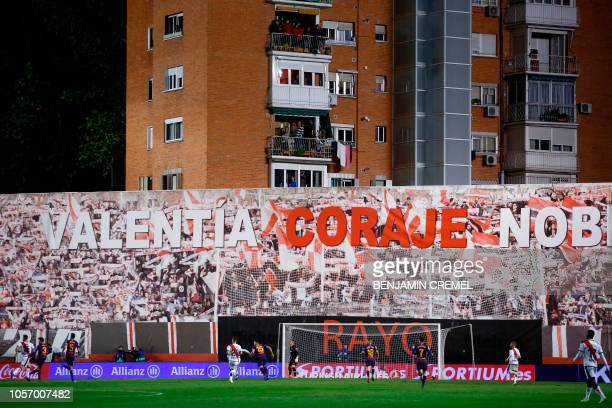 Residents of a building adjacent to the Vallecas stadium stand on their balconies to watch the Spanish league football match between Rayo Vallecano...