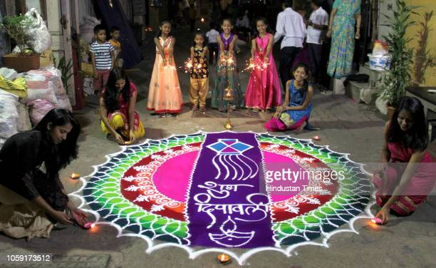 Residents of a Gawali wadi making colorful rangoli and Children bursting fire crackers during Diwali festival on November 7 2018 in Mumbai India...