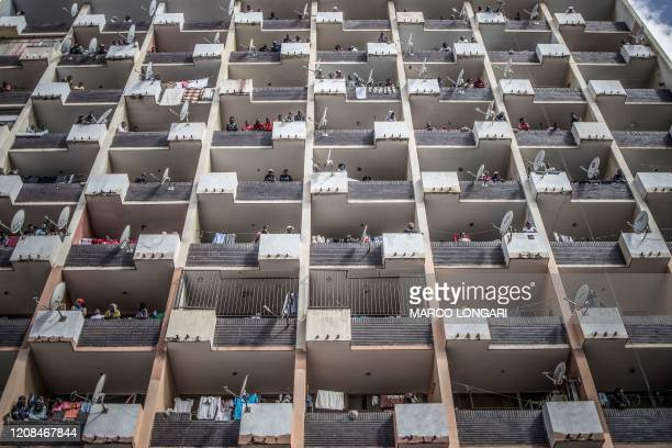 Residents of a Hillbrow, Johannesburg, building observe from the balconies on March 28, 2020 as a police operation is conducted to make sure everyone...