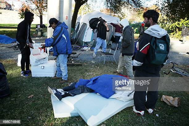 Residents of a homeless encampment near K and 27th Street NW gather as city workers try to clear up the location November 20 2015 in Washington DC A...
