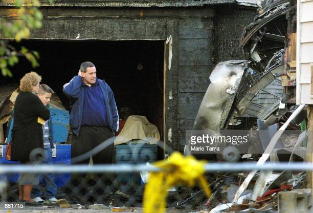 Residents of a house damaged by a falling engine from the crash of American Airlines Flight 587 stand next to the engine November 13, 2001 in the...