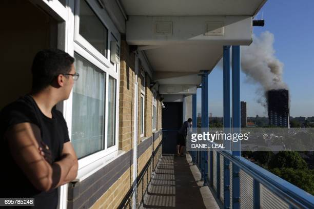 TOPSHOT Residents of a nearby council estate watch smoke billowing from Grenfell Tower on June 14 2017 in west London The massive fire ripped through...