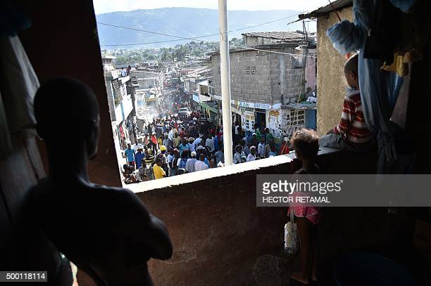 Residents of a neighborhood look at protesters marching from inside their home in PortauPrince on December 5 2015 Demonstrators marched for the...