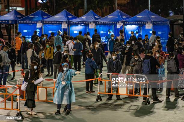 Residents of a neighbourhood wait in line for a mandatory COVID-19 test at a temporary testing site where COVID-19 cases have been confirmed in the...