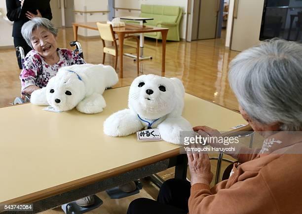 Residents of a nursing home play with nursing-care robot 'Paro' at the nursing home in Yokohama city, Kanagawa prefecture, Japan Oct. 9, 2013. PARO...