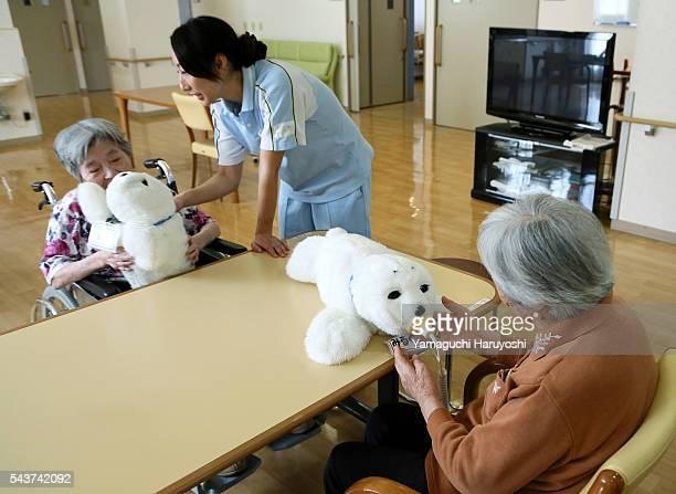 Residents of a nursing home play with nursingcare robot 'Paro' at the nursing home in Yokohama city Kanagawa prefecture Japan Oct 9 2013 PARO is the...