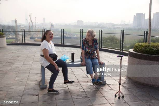 Residents of a private condominium sit at a bench with the Bandar Malaysia site one of the 1MDB projects in the background on July 29 2018 in Kuala...