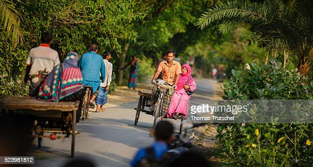 Residents of a rural region in the southwest of Bangladesh ride rickshaws and bicycles on a country road on April 10 2016 in Betal Para Bangladesh