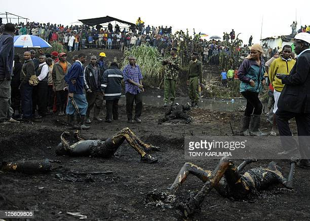 Residents of a shantee in Nairobi look at badly burnt human remains at the scene of a fierce fire on September 12 2011 that resulted from an...