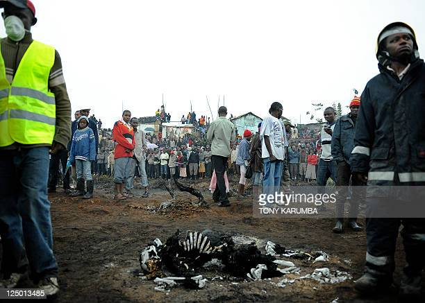 Residents of a shantee watch the charred remains of victims of a fierce fire on September 12 2011 following an explosion of a pipeline used to...