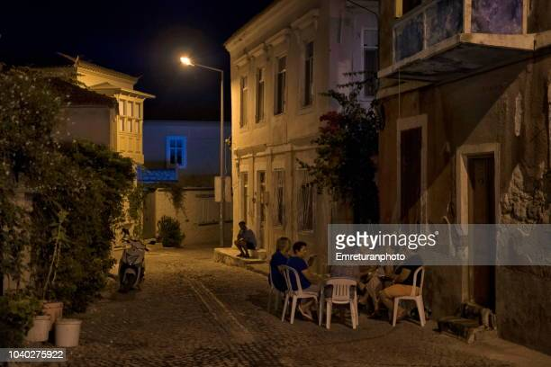 residents of alacati village sitting outside at night. - emreturanphoto stock pictures, royalty-free photos & images