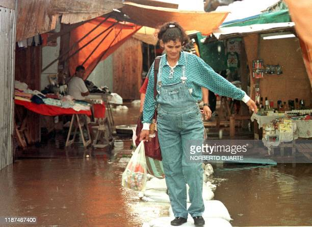 Residents of Alberdi Paraguay walk on sand bags set up in a partly flooded local market 21 April Ninety percent of the town which is located 130 Km...