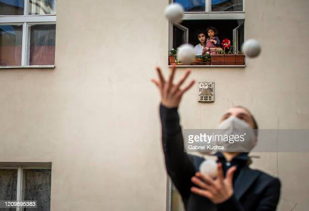 Residents of an apartment building observe from a window a juggler, member of the artistic group Cirk La Putyka, while performing to entertain...