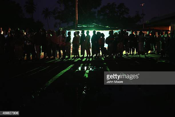 Residents of an Ebola affected township wait in line before dawn to receive family and home disinfection kits distributed by Doctors Without Borders...