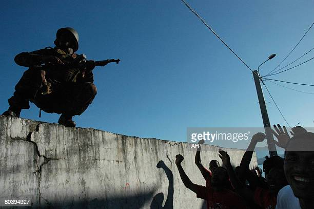 Residents of Anjouan celebrate next to a Tanzanian soldier after African Union soldiers came to shore on March 25 2008 Comoran forces and African...