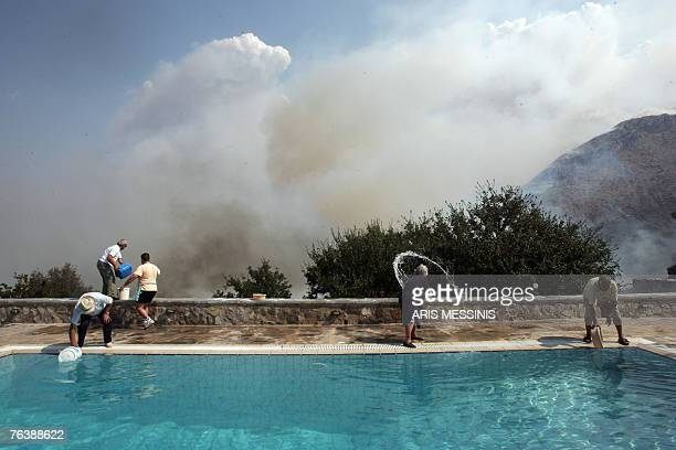 Residents of Ano Kotili village use water from a swimming pool to extinguish a fire that reaches a house at Peloponese peninsula 30 August 2007...