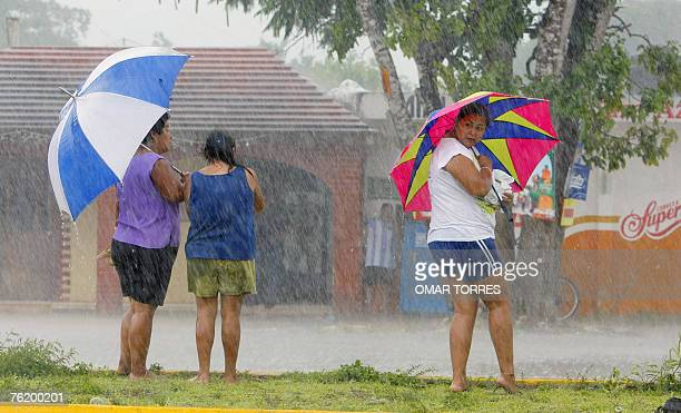 Residents of Balacar, 40 Km from the city of Chetumal, Mexico, take cover from the rain under their umbrellas, just a few hours before the estimated...