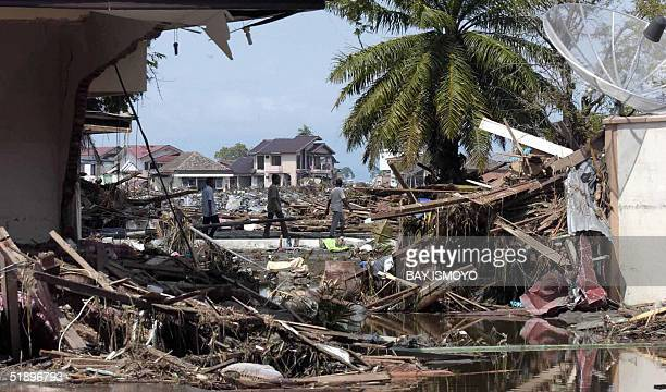 Residents of Banda Aceh walk through a scene of destruction 27 December 2004 following a devastating quake and series of tidal waves that struck the...