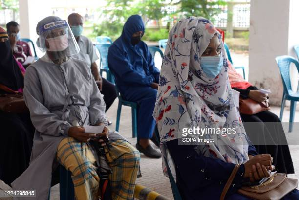 Residents of Bangladesh are seen wearing facemasks as they wait in turn to be tested for Covid-19 by the medical team. Mugda Medical College and...