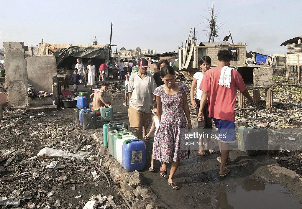 Residents of Baseco slum in Manila 25 January 2004 start their day by collecting water for their daily needs after a fire in the slum area destroyed their home earlier this month. Slums and shantytowns are endemic in the Philippine capital as thousands of rural folk are attracted to Manila, only to find they cannot get adequate housing.