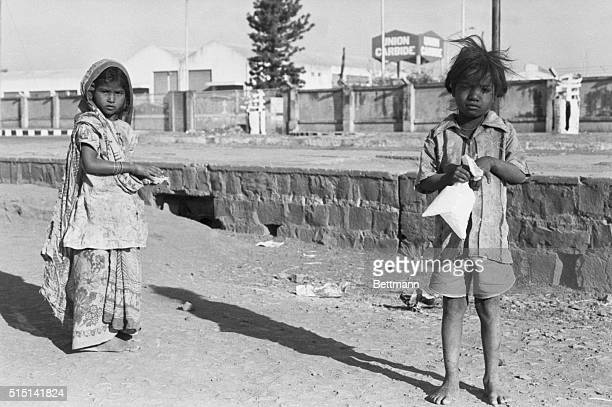 Residents of Bhopal stand in front of the Union Carbide factory gate here Earlier during the month deadly gas that was to be converted into harmless...