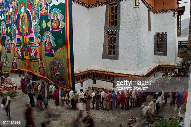 Residents of Bhutan's capital Thimpu wait in line to enter the 17th century built Simtokha Dzong monastery underneath a giant Buddhist tapestry...