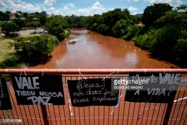 Residents of Brumadinho and relatives of victims place messages on the bridge over the Paraopeba River during a tribute to the victims one month...