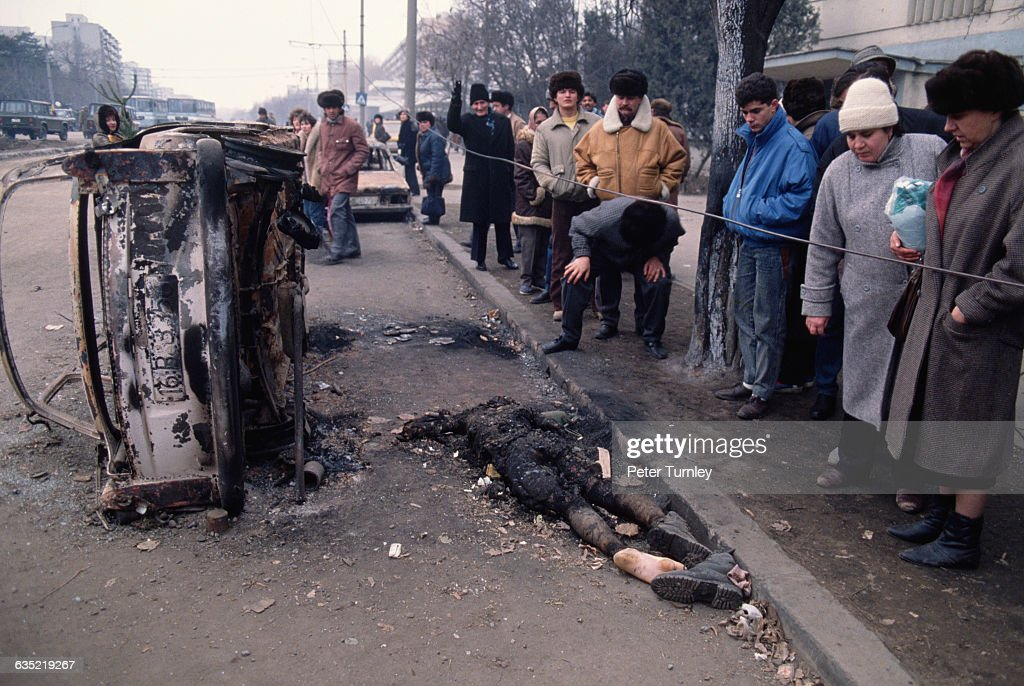 People Looking at Burned Car and Corpse : News Photo